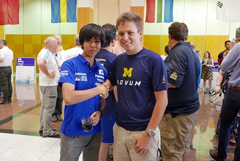 ミシガン大学チームの学生と握手するチームメンバー